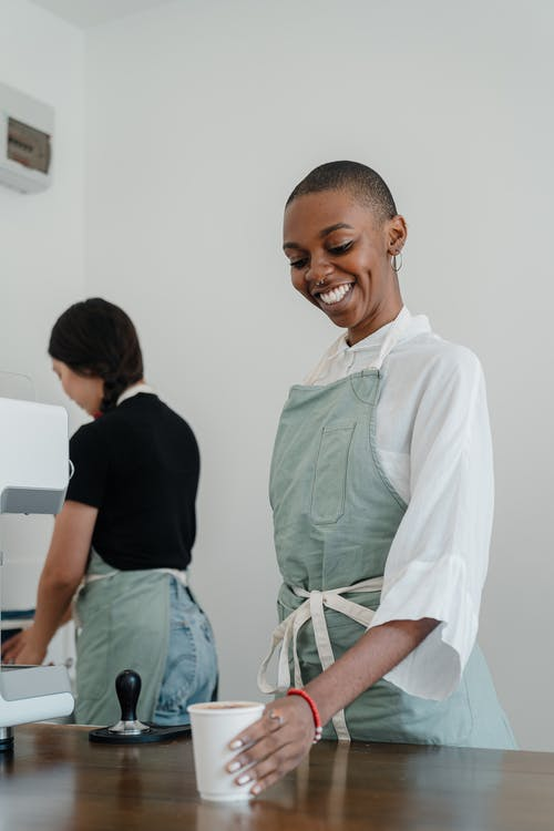 Happy young black woman with short hair wearing apron serving paper cup with coffee to go while standing at wooden counter and looking down with smile