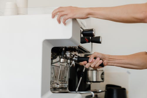 Unrecognizable female bartender adjusting portafilter in coffeemaker for preparing tasty aromatic espresso during work in coffee house