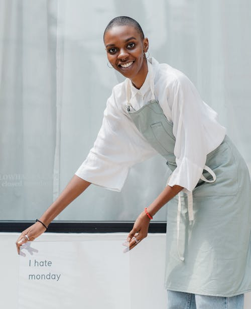 Happy black female worker setting signboard outside cafeteria