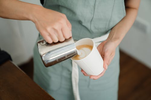 Crop barista pouring milk froth in cappuccino for client