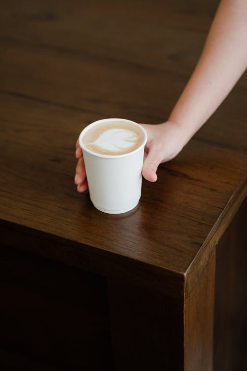 From above of unrecognizable female bartender putting paper cup with delicious latte to go on wooden counter while working in modern coffee house