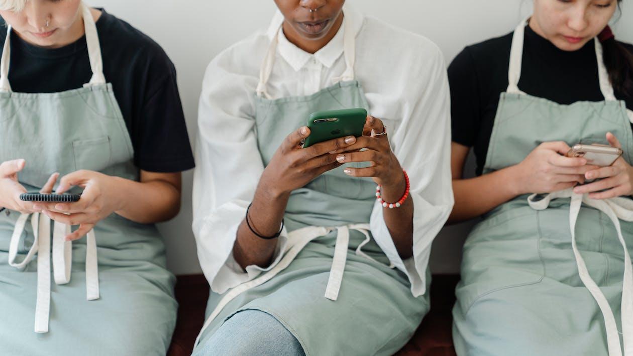 Crop focused multiethnic baristas using smartphones