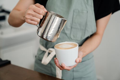 Crop bartender in apron preparing aromatic cappuccino in cup while pouring foam of milk into ceramic cup in coffeehouse