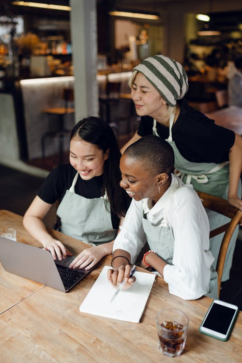 Cheerful diverse colleagues working on laptop in cafe