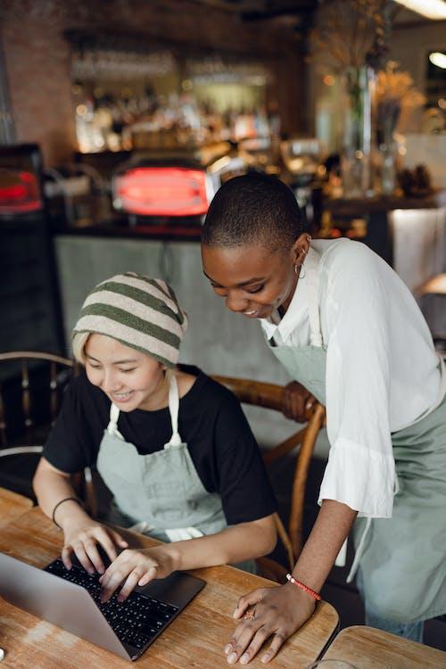 Smiling diverse baristas using laptop in modern cafe