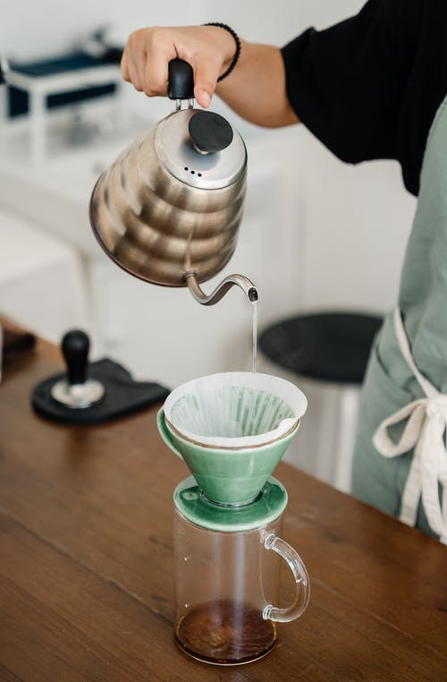 Barista pouring coffee via funnel dripper and disposable filter