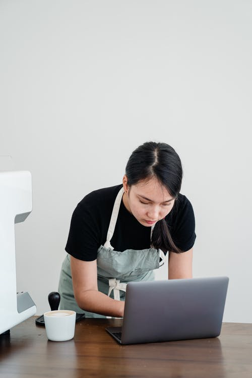 Woman in Black Shirt and Apron While Using Laptop Computer