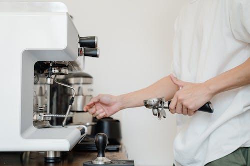 Photo of Person Standing Near Espresso Machine