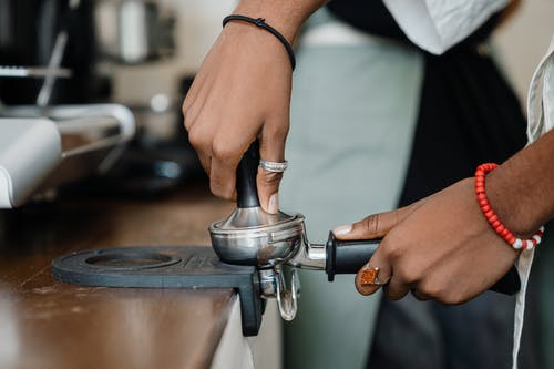 Crop barista making fresh delicious coffee using professional machine