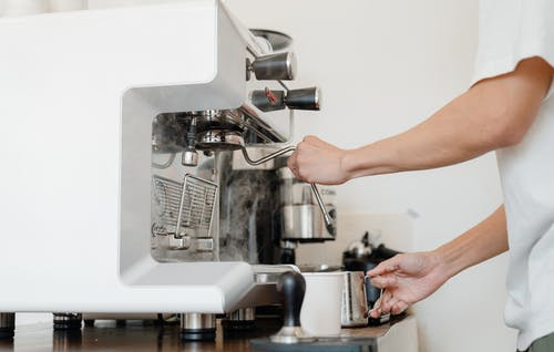 Side view crop anonymous barista in white shirt preparing to steam milk in frothing pitcher using professional coffee machine steam wand
