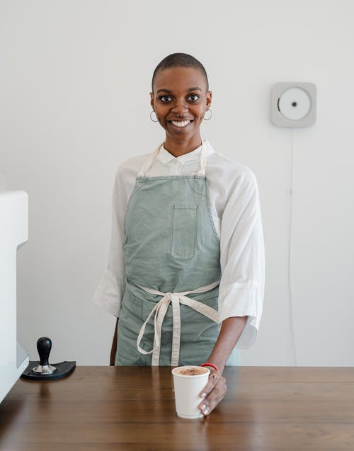 Photo of Woman in White Long Sleeve Shirt and Apron While Holding a Cup of Coffee