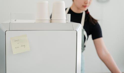 Crop woman in apron near coffee machine