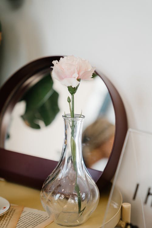 Vase with flower on table against round mirror