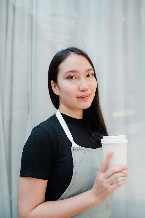 Positive waitress in apron with paper cup