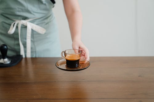 Crop barista passing cup of fresh espresso