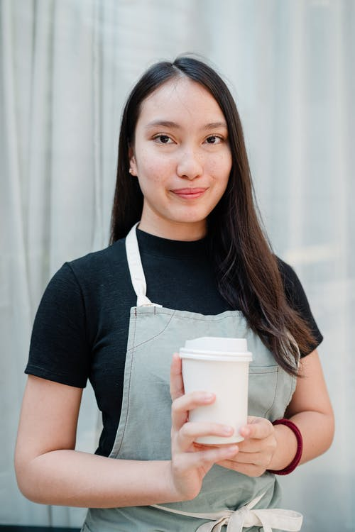 Optimistic smiling Asian waitress with white takeaway paper cup in hands standing against light blue curtains in cozy cafe and looking at camera
