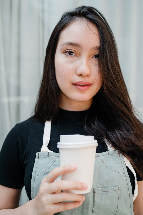 Photo of Woman Holding White Disposable Cup