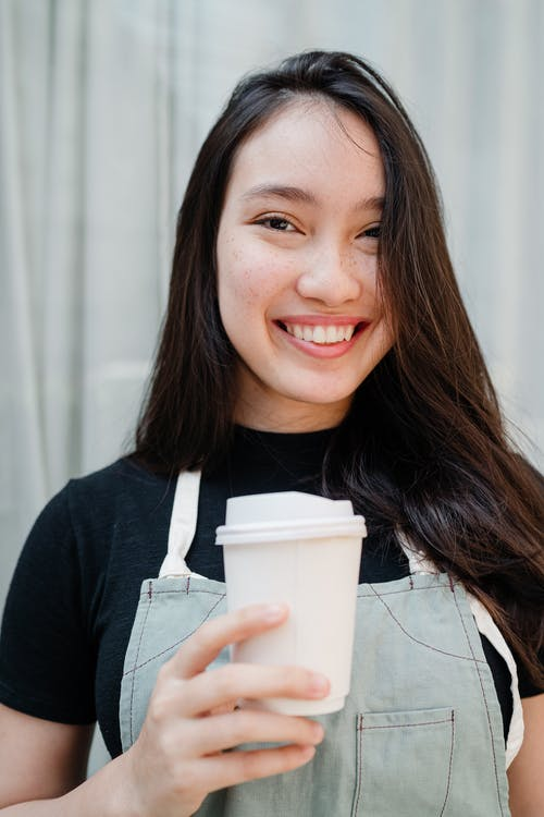 Photo of Woman Smiling While Holding White Disposable Cup