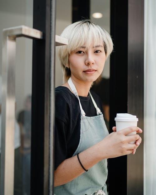 Positive young ethnic woman in apron holding cup of takeaway coffee and looking at camera