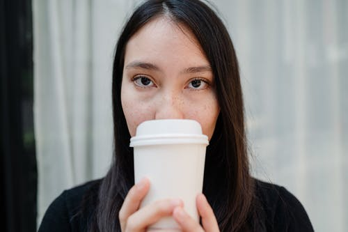 Woman Holding White Disposable Cup