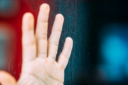 Crop unrecognizable person showing raised hand with calluses illuminated by colorful light near tree trunk