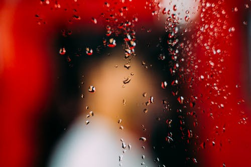 Window with water drops behind unrecognizable person