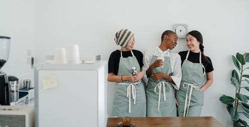 Positive young multiethnic female baristas in aprons talking and smiling while working in modern light cafeteria