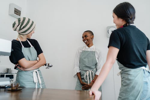 Happy young multiracial female baristas having conversation at workplace