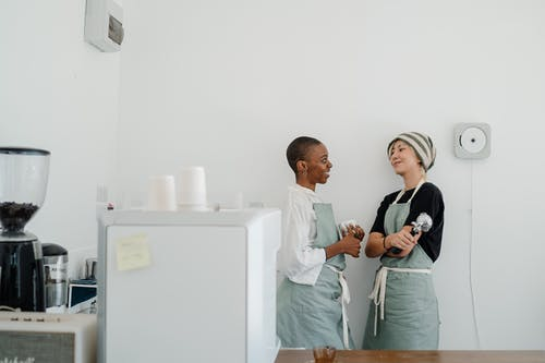 Diverse young women looking at each other while communicating during work in cafe