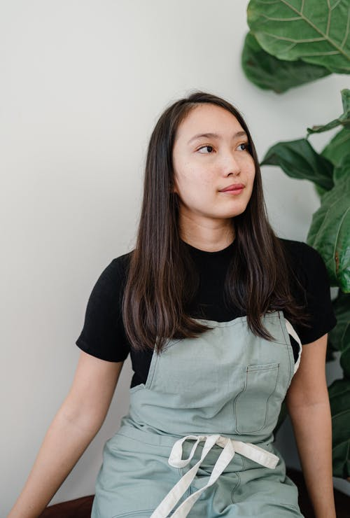 Photo of Woman Wearing Apron While Looking Away