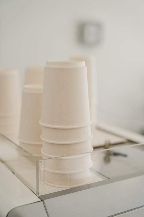 Set of various white paper cups placed on coffee machine in modern cafe