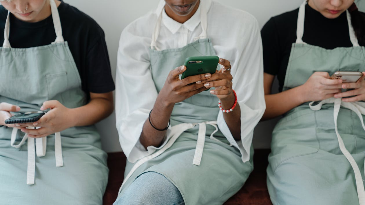 Crop female multiracial coworkers browsing mobile phones during free time