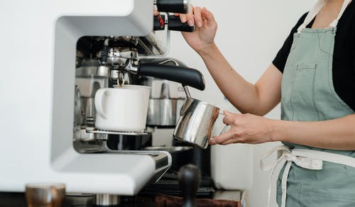 Crop young woman whipping milk using professional machine in coffee shop