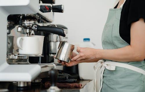 Crop young barista preparing fresh latte in cafe