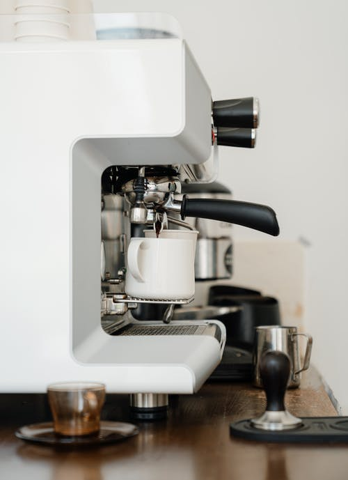 Coffee machine pouring cappuccino into cup in modern cafe