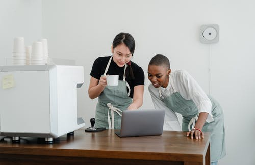 Positive young diverse female baristas in apron uniforms standing at table and watching interesting video on laptop during coffee break