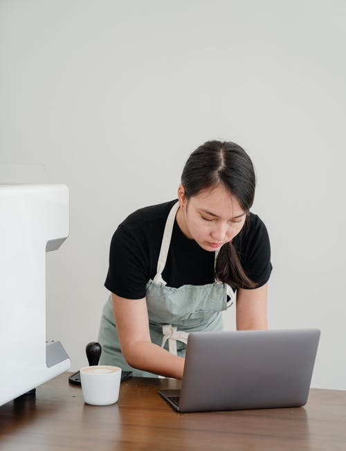 Concentrated barista using laptop at workplace