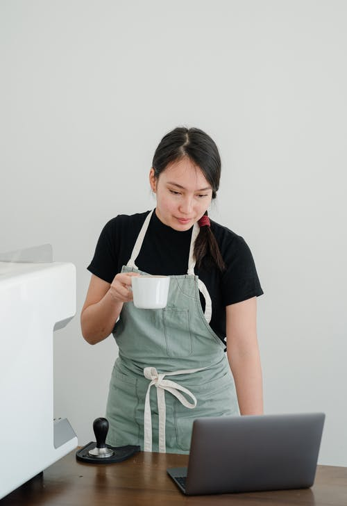 Young Asian female coffee shop worker with coffee in hand watching TV series on laptop while standing at wooden table during break