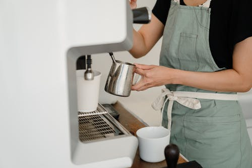Crop barista preparing coffee in cafe