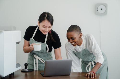 Young female baristas watching funny video on laptop during break