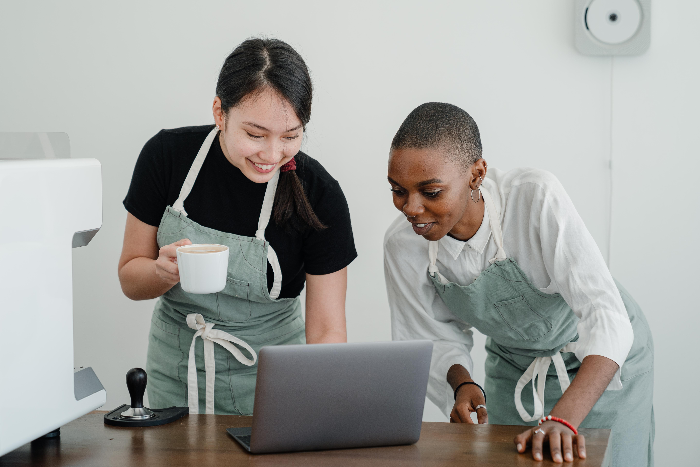 smiling multiracial baristas using laptop during coffee break