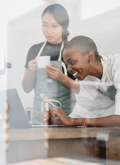 Multiethnic female baristas in aprons using laptop during coffee break