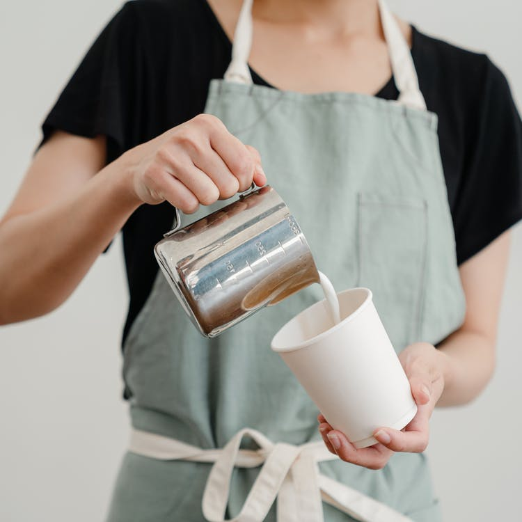 Unrecognizable female worker pouring milk into coffee cup