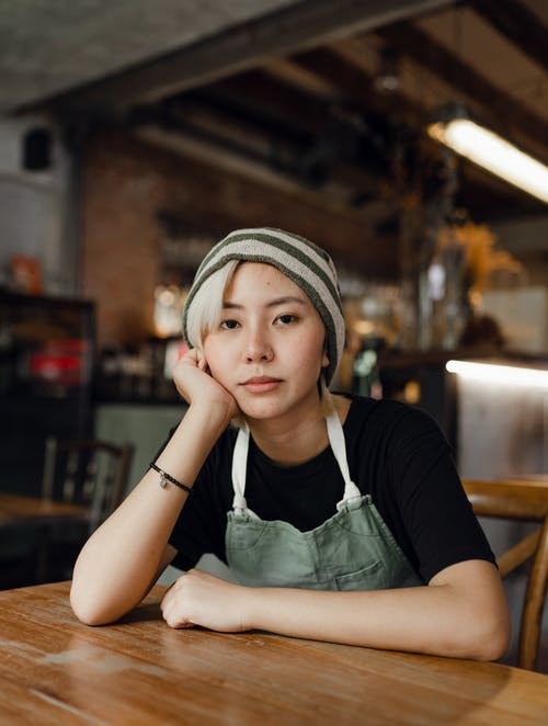 Female barista in beanie and apron resting chin on had