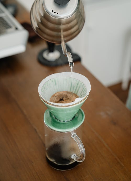 From above of process of dripping water from metal kettle into coffee filter in pour over during alternative coffee brewing