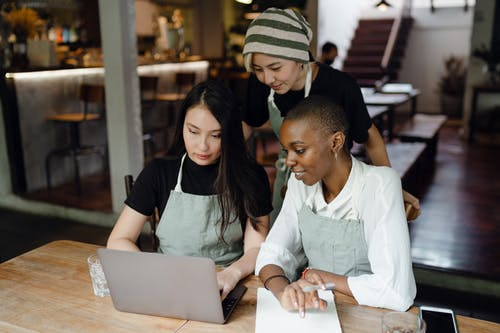Smiling multiracial female coworkers in casual wear and aprons using modern netbook while working on project together in creative cafe