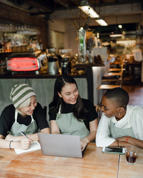 Cheerful colleagues in aprons gathering at table with laptop