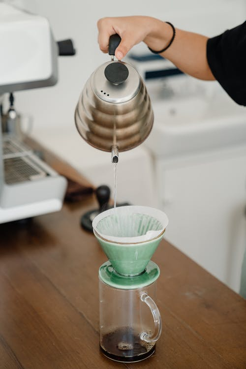 Crop barista pouring water into pourover filter