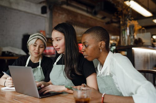 Content diverse women in aprons browsing laptop in cafeteria