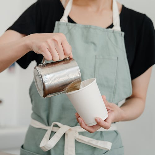 Crop barista in apron pouring milk into paper cup